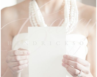 Bride looking to the side holding blank 5x7 card mockup stationery invitation for wedding