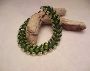 Green and light yellow flat spiral stitch bracelet with a magnetic clasp.