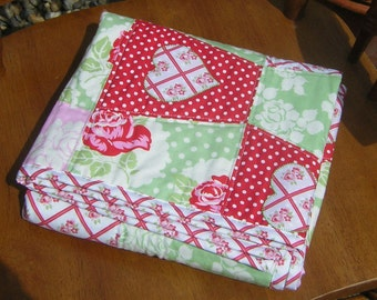 "Pretty cot quilt 42"" x 31"". Tanya Whelan designer prints, pink, green & red patchwork. Floral and polka-dot. Heart appliques. Ready to ship."