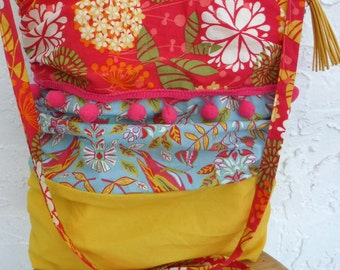 Pompom bag! Boho chic spring crossbody with mixed floral prints. Ruched sides. Comes with tassel purse charm. Pink, blue and yellow.