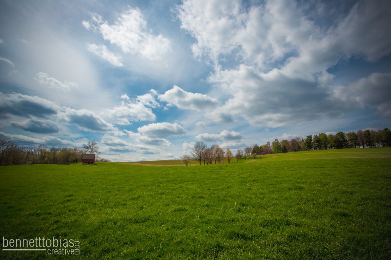 Granero rojo en un ángulo amplio campo verde casa de campo