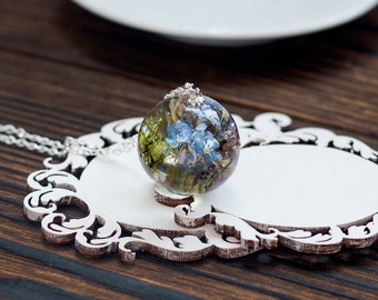 Pendant with a bouquet of forget-me-nots, moss and wild herbs.