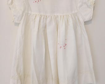 Cream vintage baby dress with lace detailing and pink flower embroidery. Approx size 2/3.