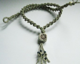Natural colored hemp necklace with high fired ceramic bead.
