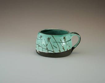 Handmade cup green on black clay with nature movite.