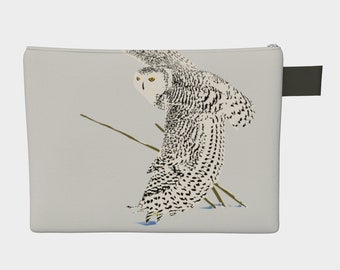 Carry-all with zipper: print of the snowy owl in flight touching the snow with his wing.