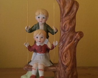 Vintage boy & girl on a swing
