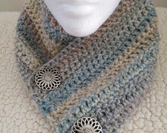 An adult soft, cozy, warm scarf crocheted in shades of gray, blue, and beige with two silver buttons