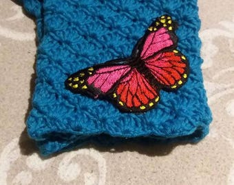 Teal crochet fingerless gloves with pinkish-red butterfly.