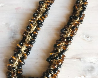 About 1980. Chain Torchon necklace and small black and ochre glass beads.