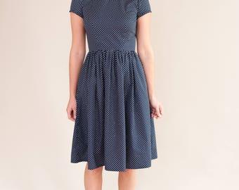 Navy spotty dress with ruffled neckline