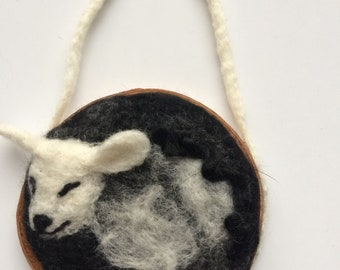 Small felted sheep needle on wood slice