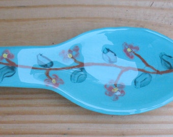 Fused glass turquoise blue  with a small flower design spoon rest.