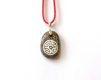 painted white labyrinth pendant with a pebble