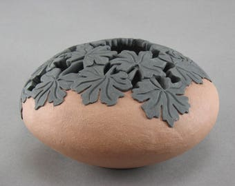 Vessel with geranium leaf carving and cut outs