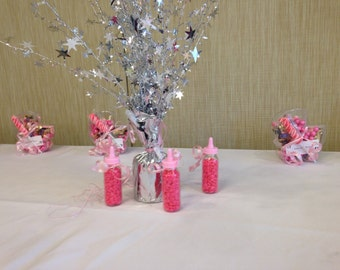 Plastic mini baby bottles filled with gum great for table decor, favors or table number settings