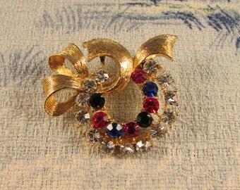 Late 1950s gold-tone ribbon bow & wreath brooch, multicoloured rhinestones