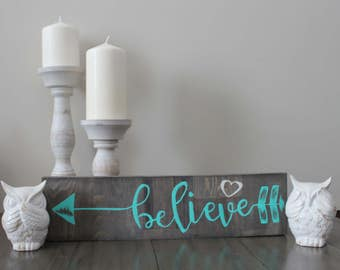 Black stained Teal believe arrow sign