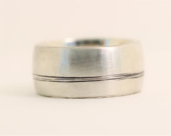Bound Together off centre  engraved lines on an 11mm wide recycled silver mans wedding style band.