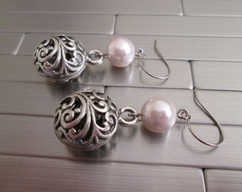 Earrings in pale pink Swarovski pearls and metal filigree charms.