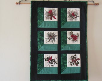 Christmas theme quilted window scenes.  Cardinals, flowers, pinecones, done in greens with black border.