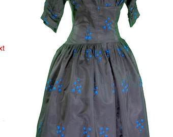 50s party dress blk taffeta embroidered in blue bells 3/4 sleeves, full shirt, fitted bodice with dropped princess waist. R & K originals