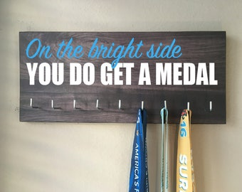 """Race Medal Holder - """"On the bright side you do get a medal"""" white and blue with dark gray wood grain background"""