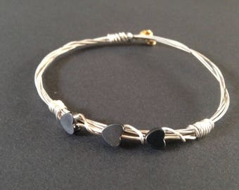 A handmade recycled silver guitar string bracelet bound  with copper wire and 4 heart shaped gemstone hermatite beads