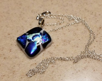 Assorted blue dichroic glass on white base pendant with sterling silver 24 inch chain.