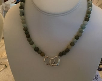 Multicolor jade necklace with intertwined sterling silver hearts as a focal point.