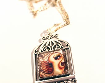 Birdcage necklace pendant with print of owl inside. Art by Susann Brox Nilsen. Silver colored. Illustration, owl, big eyes.