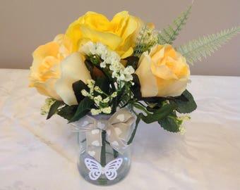 Glass jar of yellow silk flowers