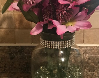 Artificial purple flowers in a glass vase with a rhinestone rim.