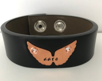 "Black leather belt bracelet cuff with a hand stamped message on a copper blank.  The message reads, ""dare."""