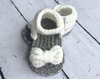Crochet baby girl bow sandals in gray and white, cotton, with gray button.