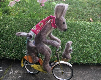 Needle felted hare on a bike with her youngsters
