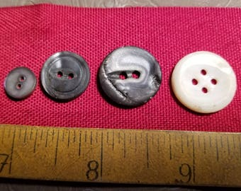 Four miscellaneous shell or other natural material buttons