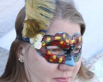 Hand painted venetian style mask with flowers and vines growing across a blue sky from the line moonlight masquerade
