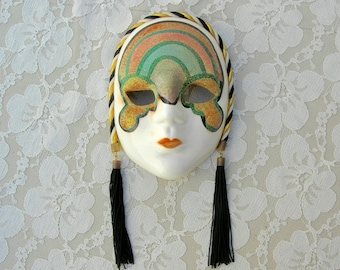 Small Mardi Gras Wall Mask, black tassels on black/gold/white twisted cord, green/gold/orange glitter mask on face, hand-painted