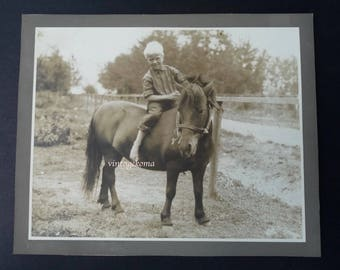 Child's photo on pony. Sepia. Horse 1940-1950. Campagne.Ferme.Champ fence. Equitation.nature.souvenir childhood. Feet blond child nudes