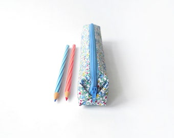 Small pencil case/zipper pouch with tiny flowers and leaves in blue, yellow and red on a white background, with a blue zip