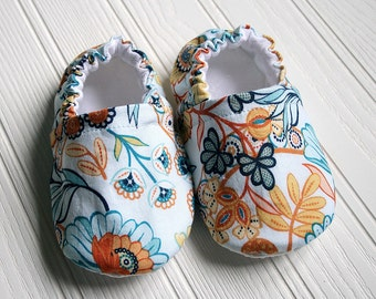 Cotton baby slippers. Cotton, flannel, grip tight fabric.  Sky blue background with navy and orange accented floral scrollwork.Made to order