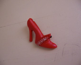 little red plastic shoe pin