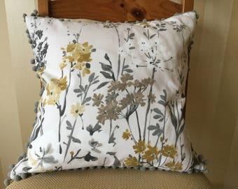 Stylish cushion with pom pom trim detail