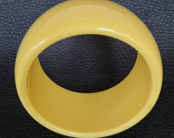 Chunky plastic muted yellow bangle.