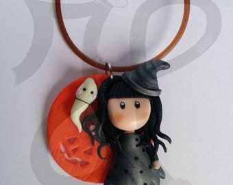 Pendant with orange base with little witch doll