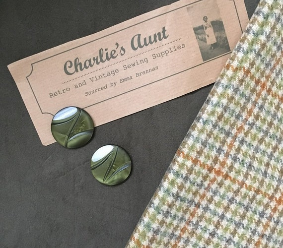 Two pieces of British fabric in tones of green and rust, one dogtooth check tweed and one cotton moleskin, plus two vintage buttons