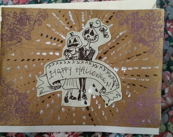"""4"""" x 5 1/2"""" handmade Halloween card, featuring a jack-o-lantern couple on the front."""