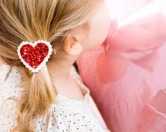 Set of 3 glitter heart clips.