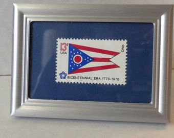 Framed picture of Ohio State Flag, framed 13 cent US mint postage stamp, in silver metal frame, collectible stamp, US Bicentennial